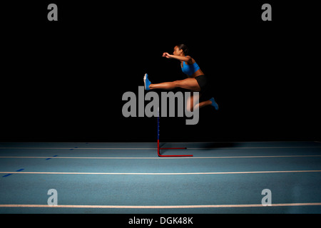 Jeunes femmes athlètes jumping hurdle Banque D'Images