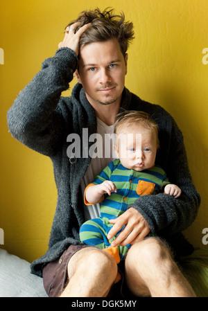 Fatigué père holding baby boy Banque D'Images
