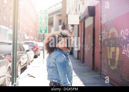 Young woman walking down street looking over shoulder Banque D'Images