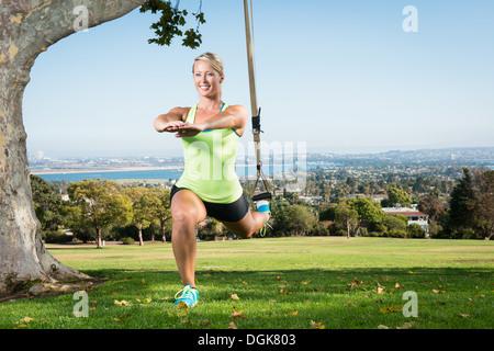 Jeune femme à l'aide d'une fente de corde en park
