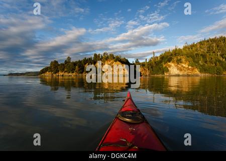 Kayak paddler se dirige vers la terre dans des régions sauvages de l'Alaska sur l'après-midi ensoleillée en été Banque D'Images