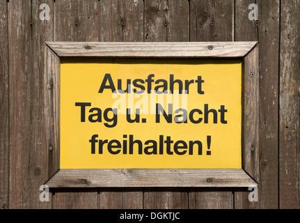 """Signer, lettrage """"Ausfahrt Tag und Nacht freihalten!', l'allemand pour """"garder jour et nuit claire!' sur une barrière Banque D'Images"""