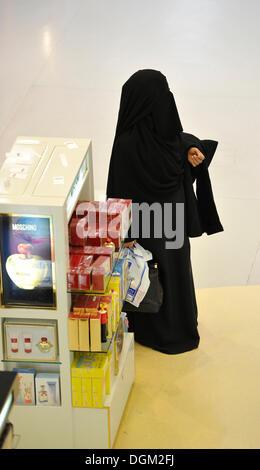 Femme qatarie en costume traditionnel abaya et voile, cosmétiques, zone franche, l'Aéroport International de Doha, Doha, Qatar, en Asie