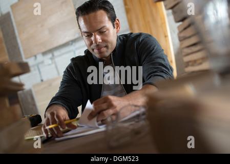 Un jeune homme dans un atelier à l'aide de papier et stylo pour tenir des registres.