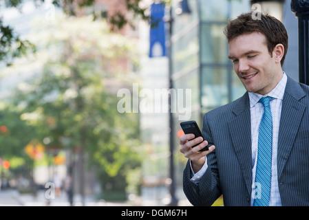 L'été. Un jeune homme en costume gris et cravate bleue. À l'aide d'un téléphone intelligent. Banque D'Images