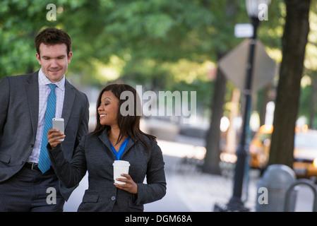 L'été. Un jeune homme en costume gris et cravate bleue marcher avec une femme dans un costume. L'homme blanc, noir Banque D'Images