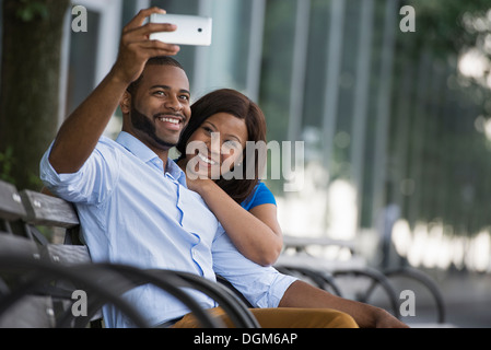 L'été. Un couple assis sur un banc, prenant une photographie selfy. Banque D'Images