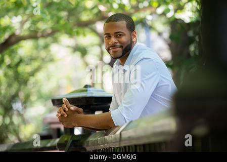 L'été. Un homme en chemise blanche s'appuyant sur une balustrade.
