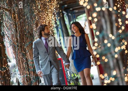 Les gens d'affaires. Deux personnes, un homme et une femme se tenant la main et marcher sous une pergola, allumé Banque D'Images