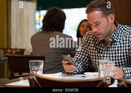 Les gens d'affaires. Deux personnes de parler les uns aux autres, et un homme à une table séparée vérifie son téléphone. Banque D'Images
