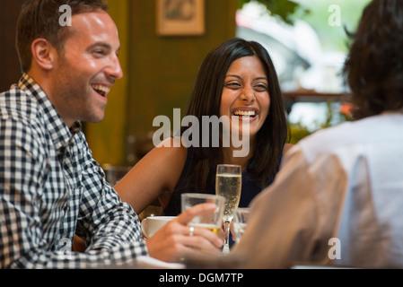 Les gens d'affaires. Trois personnes assises autour d'une table dans un bar ou café, avoir des boissons. Banque D'Images