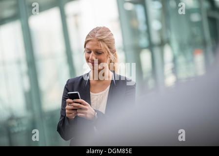 Une jeune femme blonde sur une rue de la ville de New York. Portant une veste noire. À l'aide d'un téléphone intelligent. Banque D'Images