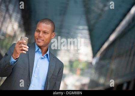 Un homme en costume, avec sa chemise déboutonnée collier. Sur une rue de la ville de New York. À l'aide d'un téléphone Banque D'Images