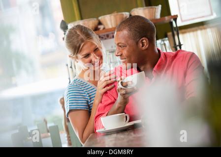 Deux personnes, un homme et une femme assis près l'un de l'autre, à la recherche à l'autre. Avoir une tasse de café. Banque D'Images