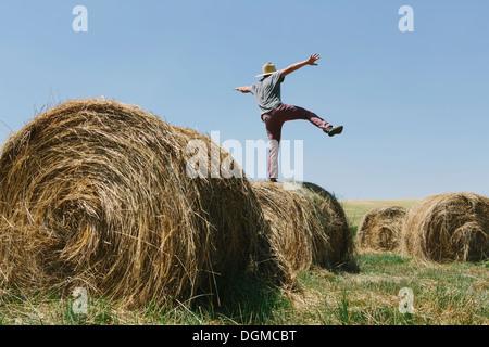 Vue arrière d'un homme en équilibre sur une jambe sur le dessus d'une balle de foin.