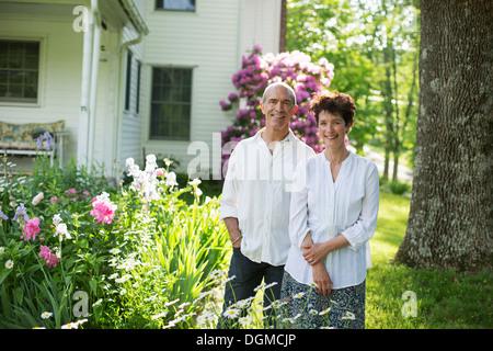 Ferme biologique. Fête de l'été. Un couple mature en chemises blanches se tenant ensemble parmi les fleurs. Banque D'Images