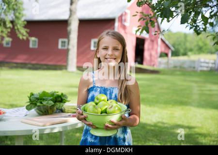 Partie de la famille. Une jeune fille aux longs cheveux blonds portant une robe d'été bleu, portant un grand bol Banque D'Images