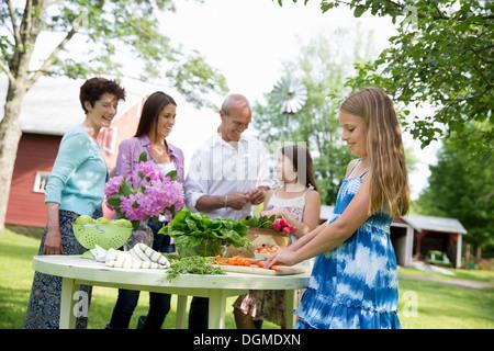 Partie de la famille. Tableau 5 personnes préparation des salades fraîches fruits partie deux filles, une jeune Banque D'Images