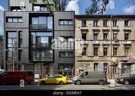 Berlin, Allemagne, le contraste entre un nouveau bâtiment à côté d'un squat Banque D'Images