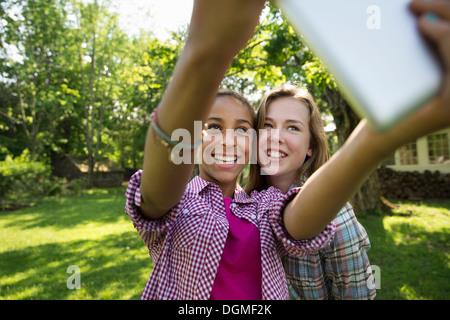 Deux filles assis dehors sur un banc, à l'aide d'une tablette numérique. Le tenant à bout de bras. Banque D'Images