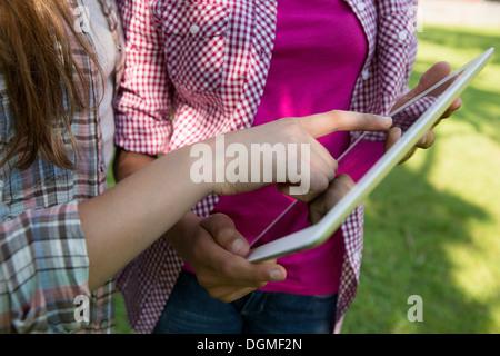 Deux filles assis dehors sur un banc, à l'aide d'une tablette numérique. Close up de leurs mains en touchant l'écran. Banque D'Images