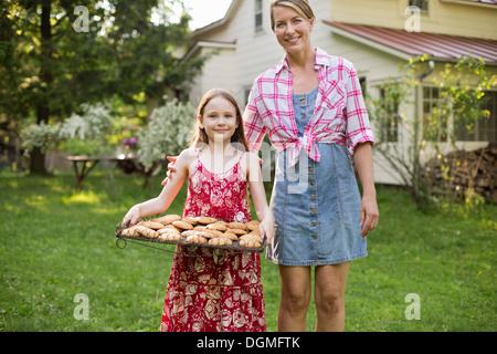 La cuisson des biscuits. Une jeune fille tenant un plateau de biscuits frais, et une femme adulte à côté d'elle. Banque D'Images