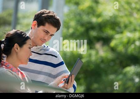 L'été. Les gens d'affaires. Un homme et une femme à l'aide d'une tablette numérique, garder le contact.