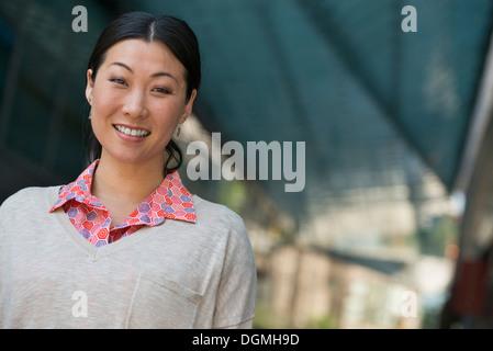 Les gens d'affaires en déplacement. Une femme dans un chandail rose et beige pull. Banque D'Images