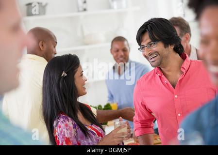 La mise en réseau d'un party de bureau ou événement informel. L'homme et la femme au centre d'un groupe. Banque D'Images