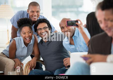 Office de l'événement. Un homme prenant une des selfies le groupe avec un téléphone intelligent. Banque D'Images
