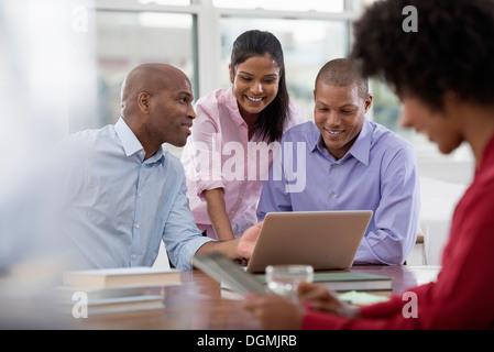 La vie de bureau. Quatre personnes travaillant autour d'une table, à l'aide de tablettes numériques et ordinateurs Banque D'Images