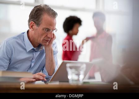 La vie de bureau. Un homme assis à un ordinateur portable s'appuyant sur un bras, et deux femmes à l'arrière-plan.