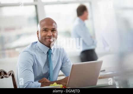 La vie de bureau. En homme d'une chemise et cravate assis à un bureau, à l'aide d'un ordinateur portable.