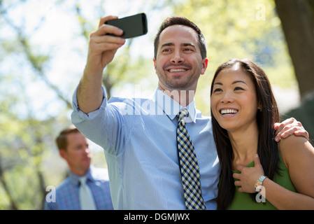 Un couple avec un téléphone intelligent, côte à côte. Un homme dans l'arrière-plan. Banque D'Images