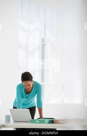 L'entreprise. Une femme se penche au-dessus d'un bureau à l'aide d'un ordinateur portable. Banque D'Images