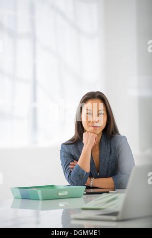L'entreprise. Une femme assise, de détente avec son menton sur sa main.