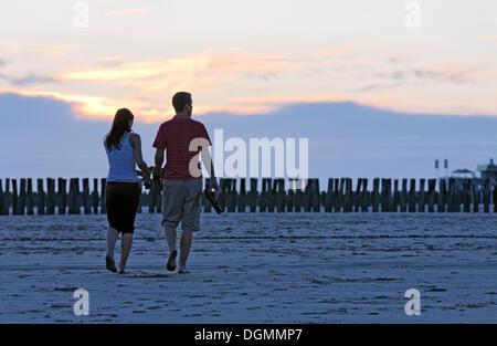 Jeune couple de prendre une marche sur la plage au coucher du soleil, Zoutelande, presqu'île de Walcheren, province Banque D'Images