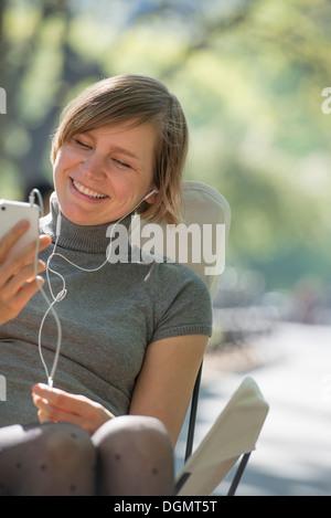 La vie en ville. Une femme assise dans un fauteuil de camping dans le parc, l'écoute de musique portant des écouteurs. Banque D'Images