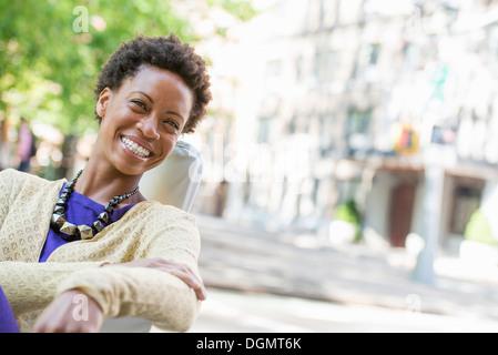 La vie en ville. Une femme assise à l'air libre dans un parc de la ville.