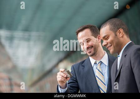 Ville. Deux hommes en costumes, regardant un smart phone, smiling.