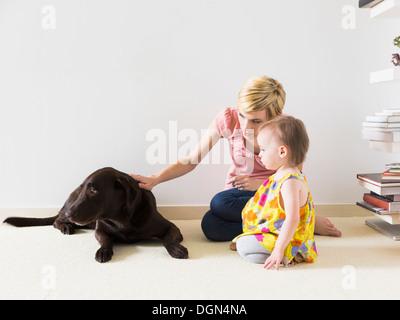 Mère avec bébé fille (4-5) Playing with dog Banque D'Images
