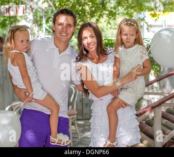 Portrait jeune famille de quatre dans le café avec white baloons Banque D'Images
