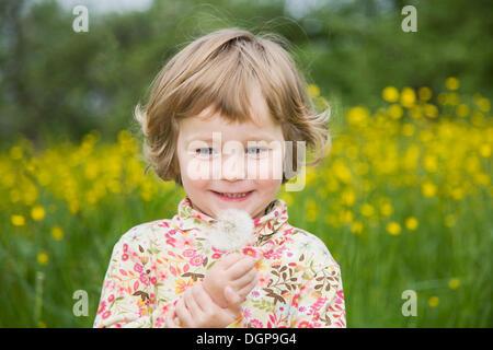 Happy girl holding un pissenlit réveil dans sa main, portrait Banque D'Images