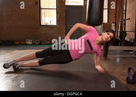 Jeune femme exerçant sur le tapis de gym