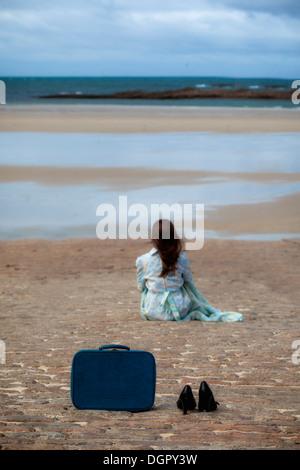 Une valise et chaussures noires sur un feuillet, dans une distance est assise une femme Banque D'Images