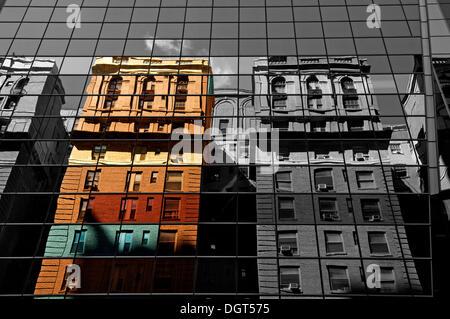 Les maisons sont reflétées dans la façade en verre d'un gratte-ciel, New York City, New York, United States Banque D'Images