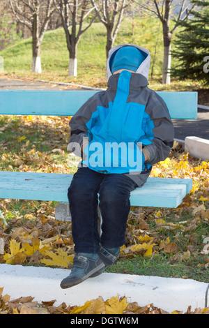 Petit garçon assis sur un banc de parc en bois avec un bonnet bleu tricoté la dissimulation de son visage et la Banque D'Images