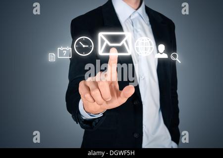 Portrait of young handsome businessman touching futuristic interface Menu avec icônes numériques différents. Isolé Banque D'Images