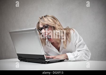 Femme blonde en colère crier contre un ordinateur portable Banque D'Images