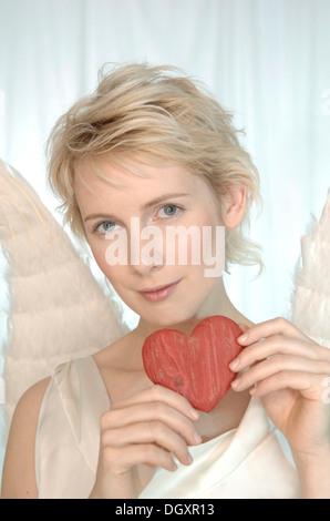 Femme blonde avec des ailes d'anges, tenant un coeur en bois Banque D'Images